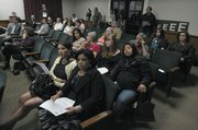 Area residents, including Sergio Romero's mother, Guadalupe Romero (foreground), listen during Thursday's presentation on Milpas Street safety