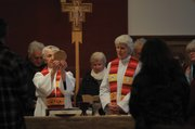 Reverend Suzanne Dunn (left) consecrates the Holy Eucharist at Palm Sunday service as Reverend Love looks on. They invite members of the congregation to join them at the altar in saying the prayer converting the wafer and wine into the body and blood of Christ.