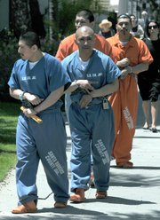 Front to back: Miguel Marquez, David Roldan (showing a Westside gang sign), Daniel Cervantes, and Victor Arroyo leave the courthouse after their sentencing on May 29, 2012