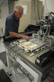 Dean White demonstrated a robot-like instrument that prepares silicon tiles for wire bonding. These wafer-like tiles trace the radioactive decay that results from colliding particles in the LHC.