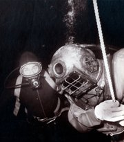 Dan Wilson decompressing off the east end of Santa Cruz Island on November 3, 1962 during the ascent from his record breaking dive to 400' using oxy-helium as a breathing gas. The SCUBA diver in the background is one of several Brooks Institute students that acted as safety divers on the decompression stops.