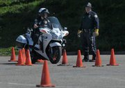 Officer Tiffany Keller navigates a training course at Earl Warren Showgrounds with Jaycee Hunter looking on.