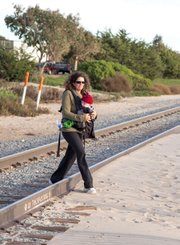 A woman and her baby cross the rails near Santa Claus Lane.