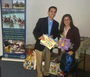 Circle V Ranch Camp & Retreat Center Director Ray Lopez gratefully accepts the donation of 2,112 children's books along with 453 items of arts & craft supplies from 16-year-old Isabella Virgen, member of the Girl Scouts of Greater Los Angeles Troup 581 from San Marino.