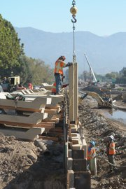 <b>MEN AT WORK:</b>  Construction crews work on the San Jose Creek channel along Highway 217.