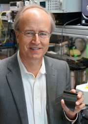John Bowers, UCSB professor of electrical and computer engineering, and of materials, holds a piece of a wafer of hybrid silicon lasers and photodetectors, for use as optical interconnects for data centers and telecommunications.