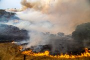 Wind-swepped flames threaten to overrun Oso Canyon.