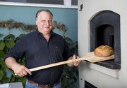 Santa Barbara Sourdough's Stephen Meyer takes a loaf out of the woodfired oven at Goodland Kitchen