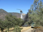 Quick response keeps the fire from spreading into the nearby brush.