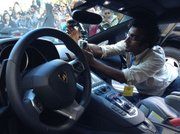 Anand Varma attaches a GoPro camera to one of the donated Lamborghinis.