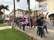 """<b>HERE AND HEARD:</b> Chanting """"No Justice, No Peace"""" and """"S-BP-D, no police brutality,"""" about 60 anti-gang-injunction activists affiliated with PODER marched down State Street and into the City Council pews."""