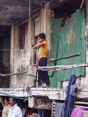 A young boy stands outside of what remains of his parents' home, watching the monks give their blessing.