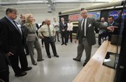 Deployable Space Systems president Brian Spence briefs NASA Administrator Charles Bolden and Congressmember Lois Capps on his company's Roll-Out Solar Array