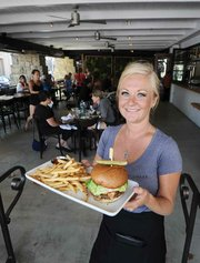 <b>SUB-$10 BURGER:</b>  Benchmark Eatery's Allison Kearney presents the restaurant's affordable burger, which symbolizes the Bennett family's desire to serve all classes of Santa Barbarans.
