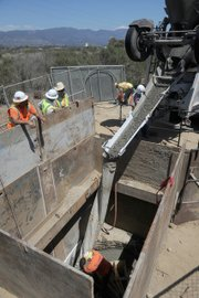 Cement is poured for the construction of a manhole located on the new pipeline.