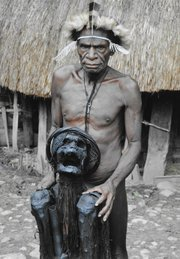 """A Lani tribesman shows a mummy of a """"big man"""" who was important in the village. The mummy lives in his own hut and is asked questions of importance by the village when needed. Harris said he only knew of three mummies through out the highlands."""