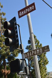 A new street sign hangs above the old version