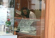 A Churchill Jewelers employee inspects a smashed display case
