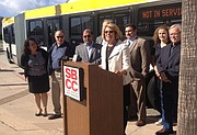 SBBC president Lori Gaskin presents one of the new articulated buses alongside the MTD board of directors and the SBCC student body president.