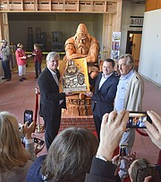 Peter Taksoe-Jensen (left), Rene Kaerskov (center), and Bent Olsen, of Olsen's Danish Village Bakery, pose with a cake and statue of Danish mythic hero Holger Danske.