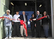 City officials and project manager Bob Roebuck (second from left) cut the ribbon on power project.
