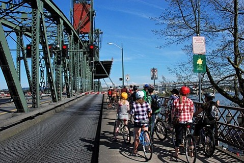 A score of kids waiting safely in the bicycle margin at the Hawthorne lift bridge in Portland, Oregon.