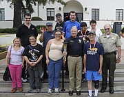 SPBD Chief Cam Sanchez (center) and Lt. Butch Arnoldi with the Sheriff's Department meet with Special Olympics athletes.