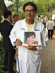 Dr. Robert Olvera holds a photo of his daughter, who died while suffering from leukemia.