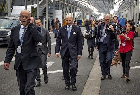 COP21 President and French Foreign Minister Laurent Fabius (center), pictured walking between conference halls at Le Bourget, will take center stage in the days ahead as he rides careful shotgun over the final negotiations and works to broker peace between disagreeing nations.
