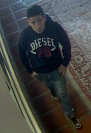 Wearing a Diesel sweatshirt, one suspect is caught eyeing a security camera.