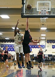 <b>CHARGER COUNTRY:</b> Marcellous Gossett (20) puts the ball off the glass over San Marcos center Jackson Stormo during a showdown that packed the Dos Pueblos gym.