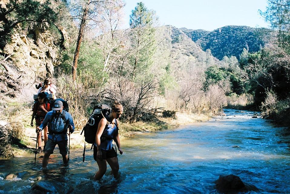 Backpackers wade across Manzana Creek.