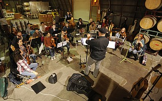 Adam Phillip leads the Folk Orchestra in a practice session at Telegraph Brewery.
