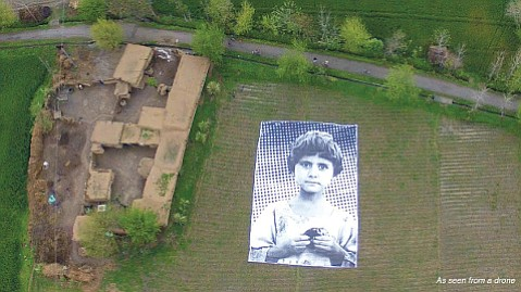 "HUMANITY BELOW:  Artist collaborative #NotABugSplat created an enormous poster to show drone operators who they were bombing. The parents of the girl photographed were killed in a drone strike, members of the ""bug splat,"" which is military jargon for anticipated civilian casualties."