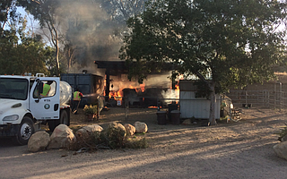County Transfer Station employees Bill Tonoli (in cab) and Chase Deasde (on hose) held the fire down with water from a dust control truck until firefighters could arrive to Hearts Therapeutic Equestrian Center.