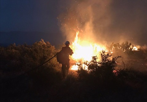 Fire crew member on the Wasioja Fire Saturday night, one of several blazes around the county just as high fire season is called.