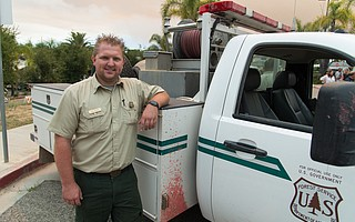 Dave Dahlberg poses with his Forest Service patrol truck, still splashed with fire retardant from the afternoon of the rescue.