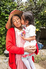 Brigida de la Cruz Mendez gets a kiss from granddaughter Esmerelda Gonzales Mendez.