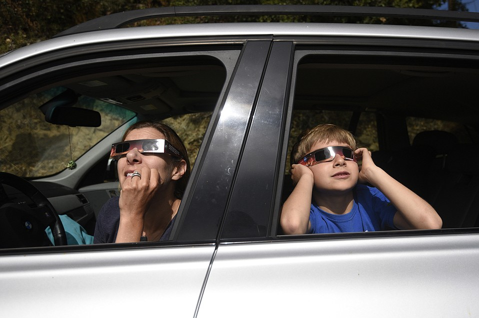 "Darian Bleecher and her son Felix watch the partial solar eclipse as seen from Stagecoach Road. Even with the glasses, Felix says, ""It's really bright."""
