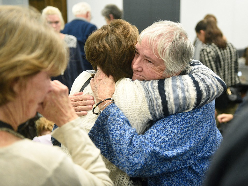 An Open Alternative School (OAS) founding educator, Gloria Liggett embraces a fellow supporter after the Board of Education voted unanimously to close the 42-year-old institute of alternative education.