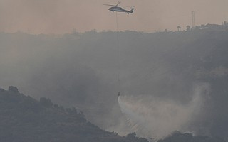 Helicopters douse the western flank of the Thomas Fire as it creeps westward toward Highway 150 and Bates Road on Thursday morning.
