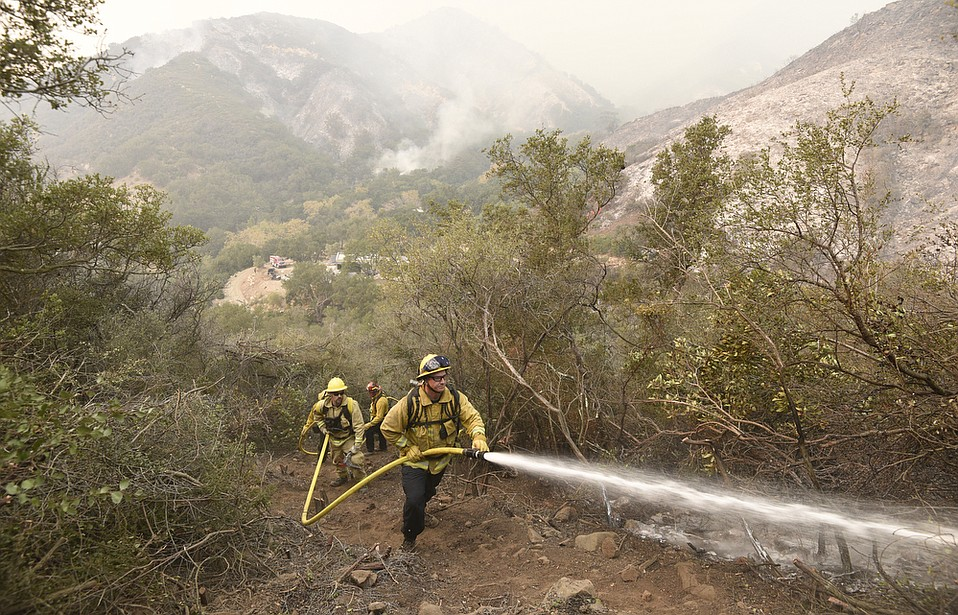 Garth White, with a crew from Bend Oregon City firefighters, works a hose alongside members of Arroyo Grande Hotshots, Santa Lucia Crew Seven and Vandenberg Hotshots working to cut a fire break up steep terrain in Toro Canyon. (Dec. 12, 2017)