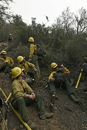 Members of Arroyo Grande Hotshots, Bend Oregon City firefighters, Santa Lucia Crew Seven and Vandenberg Hotshots working to cut a fire break, up steep terrain in Toro Canyon, welcome some water dropping helicopters after being 'bumped' back down the hill a bit 'into the black' burned area when flames shifted in their direction. (Dec. 12, 2017)
