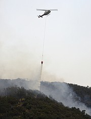 Water dropping helicopters, held back for most of the day due to poor visibility, give some much needed protection to firefighters working to cut a fire break, up steep terrain in Toro Canyon. (Dec. 12, 2017)