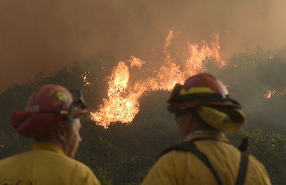 Cal Fire firefighters from Norco, California work to defend homes near Casitas Pass on the morning of Monday, December 11.