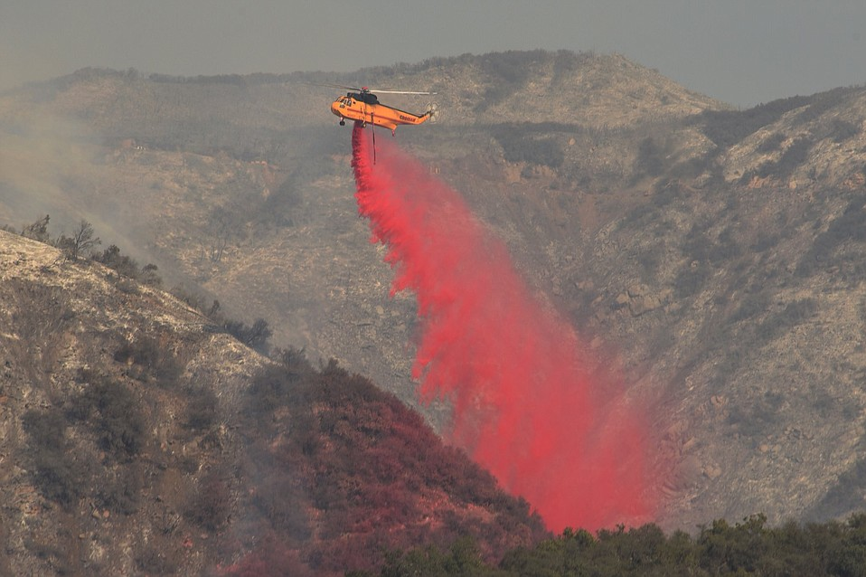 A retardant-dropping Sikorsky S-61 adds to the ground efforts ongoing to slow the Thomas Fire at San Ysidro Canyon.