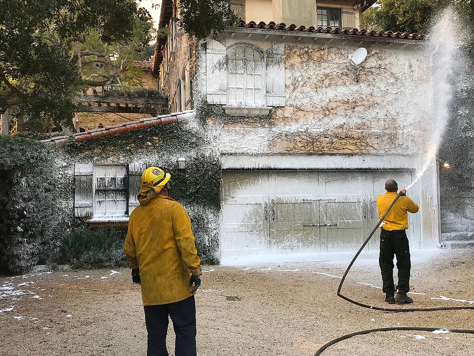 Private workers with Consumer Fire Products spray white biodegradable foam on a home to prepare for the approaching Thomas Fire.