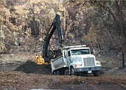 County workers open up a debris basin to contain floodwaters in an area burned by the Thomas Fire.