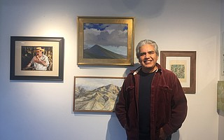 Arturo Tello stands next to his painting of Montecito Peak, one of the many paintings donated to benefit Thomas Fire victims through a silent auction at the Porch gallery.