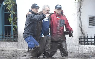 Jason Copus (left) and Mark Olson help Steve Wrolstae through thick mud on Coast Village Road (Jan. 9, 2018).